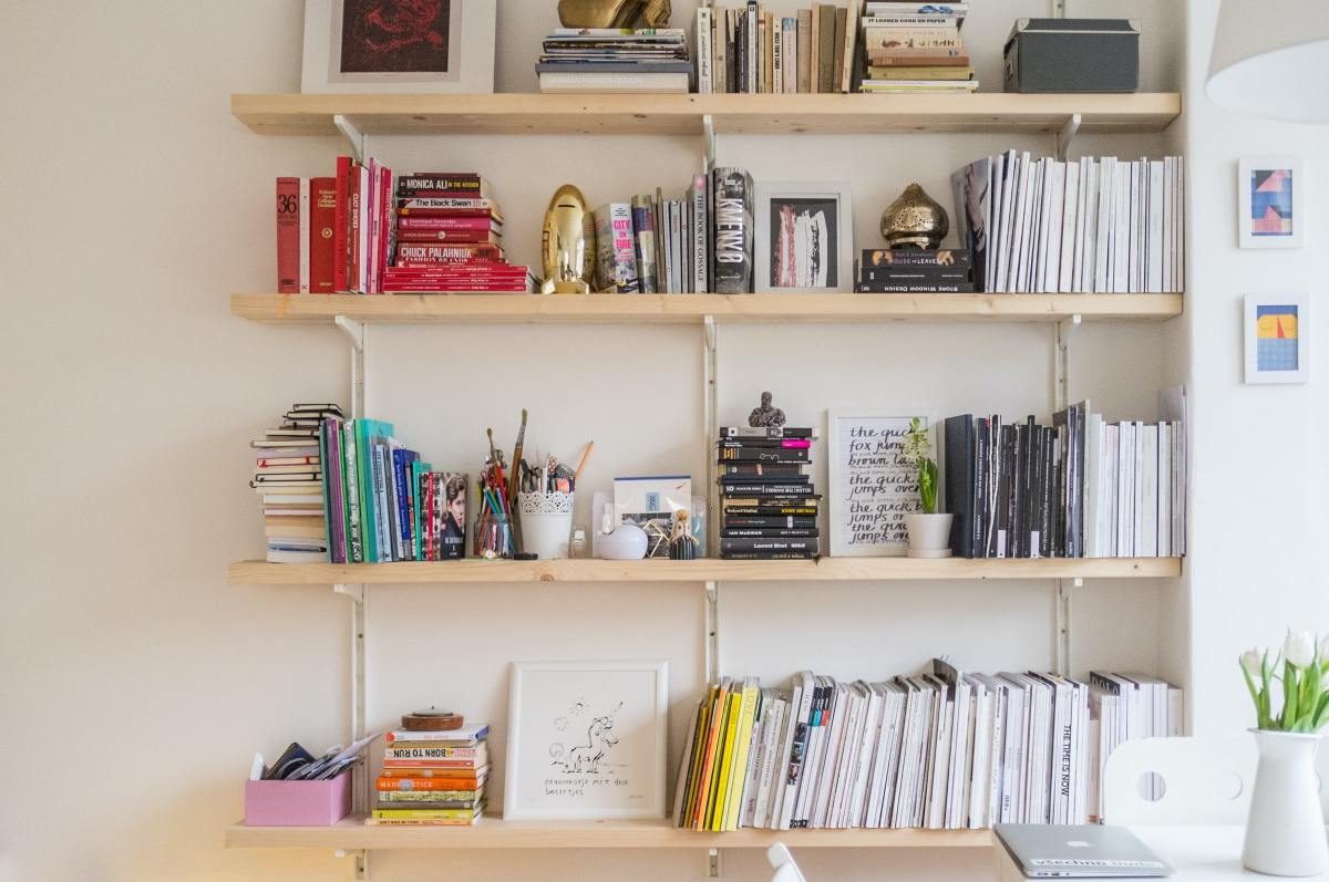 Multi-colored books and succulent plants sit on four wood shelves